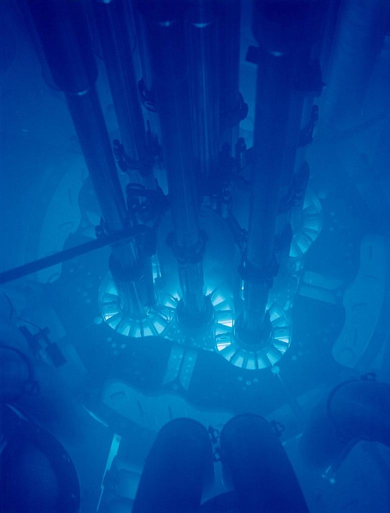 Cerenkovstraling rond een reactorkern. Deze straling, veroorzaakt door subatomaire deeltjes doe sneller reizen dan het licht in (hier) water, komt vaak vrij bij de opwekking van kernenergie.