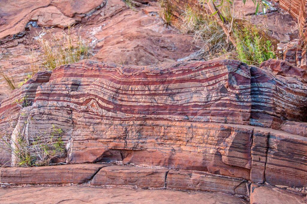 De lagen ijzeroxide zijn stille getuigen van de Grote Oxidatie: bloei- en afsterfgolven van groene, zuurstofproducerende algen. Dit veroorzaakte de grootste uitsterfgolf ooit, maar leidde tot meercellige, zuurstof ademende dieren zoals wij. Bron: Wikimedia Commons, gebruiker PDTillman
