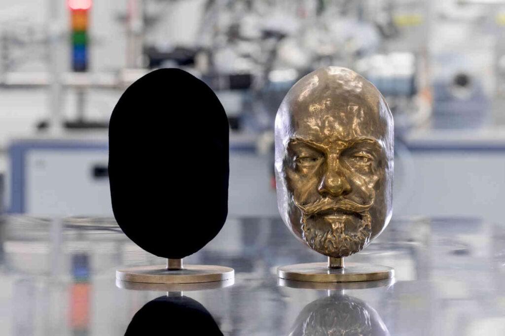 Beide maskers zijn identiek. Het linker masker is met Vantablack behandeld, waardoor het verandert in een zwarte blob Niets. Bron: Surrey Nanosystems, voorlichtingsmateriaal